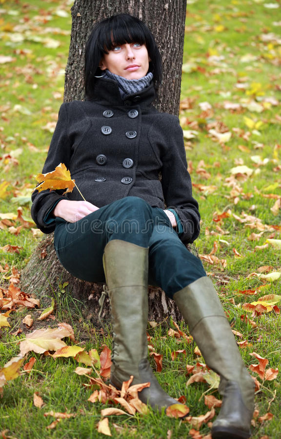 Beautiful young woman sits near the tree in park stock photos