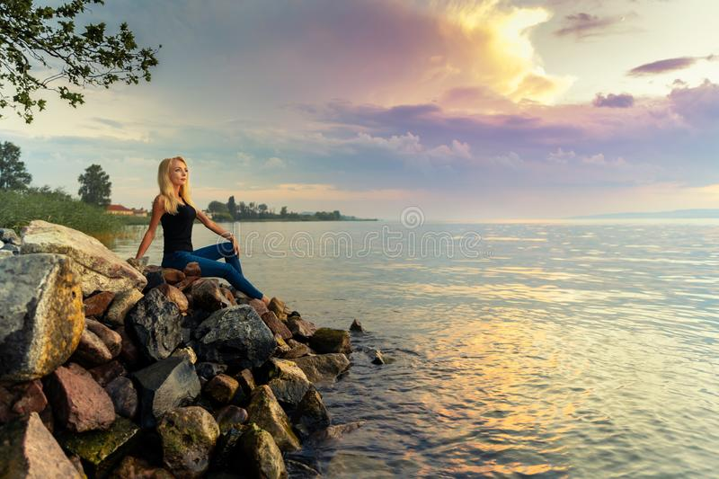 Beautiful young woman sits on the rocks by the Balaton lake stock images