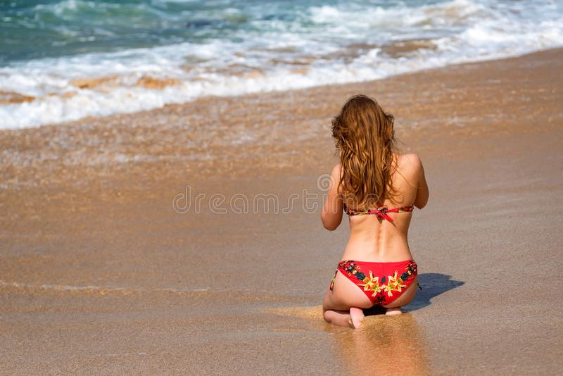 Beautiful young woman sits on sand of beach stock photos