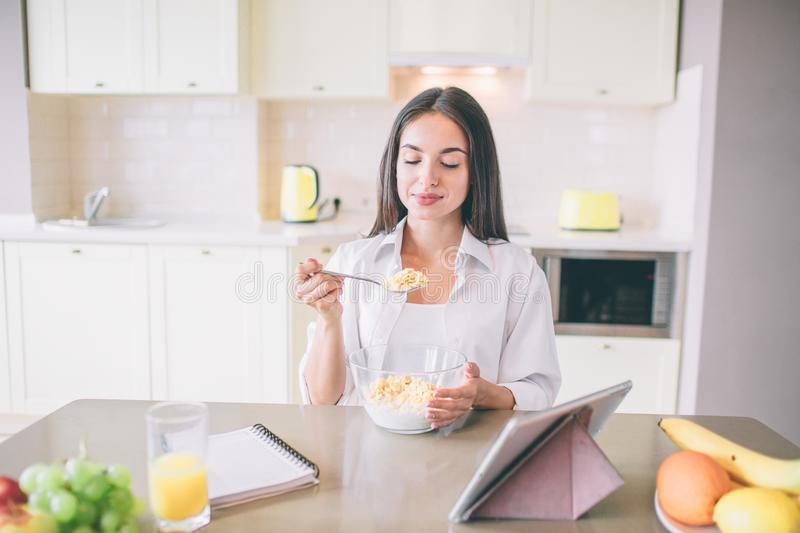 Beautiful young woman sits at table and eats milk with corn flakes. She holds spoon with it. Girl is looking at spoon stock photo