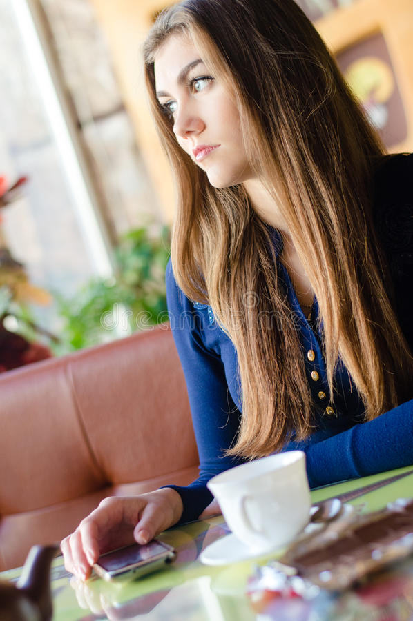Beautiful young woman sitting alone in cafe waiting for phone call royalty free stock photography