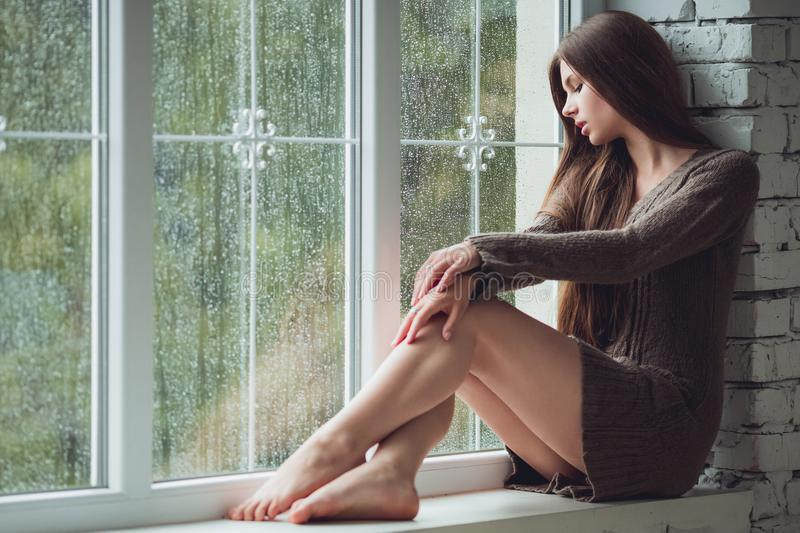 Beautiful young woman sitting alone near window with rain drops. and sad girl with long slim legs. Concept of royalty free stock photography