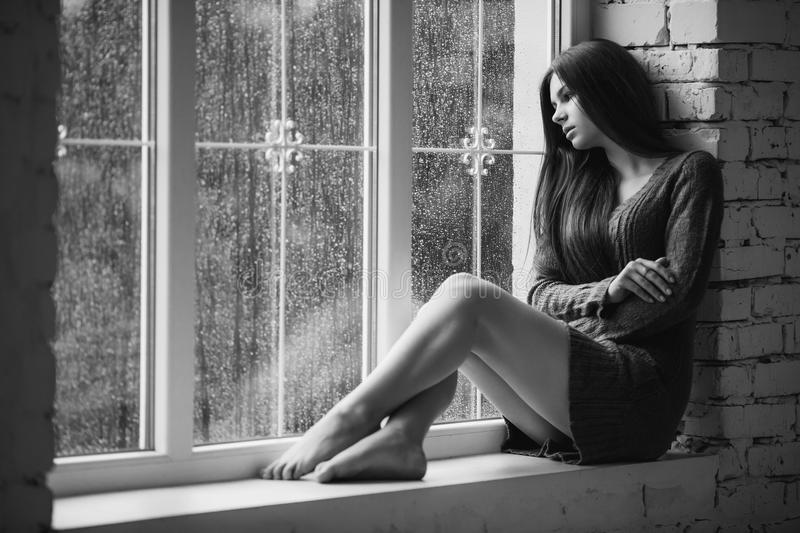 Beautiful young woman sitting alone near window with rain drops. and sad girl with long slim legs. Concept of royalty free stock image