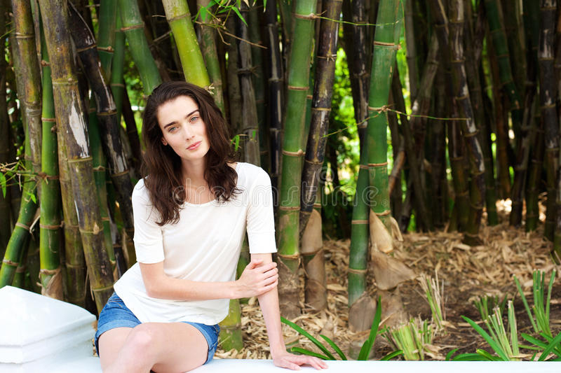 Beautiful young woman sitting by bamboo trees stock photos