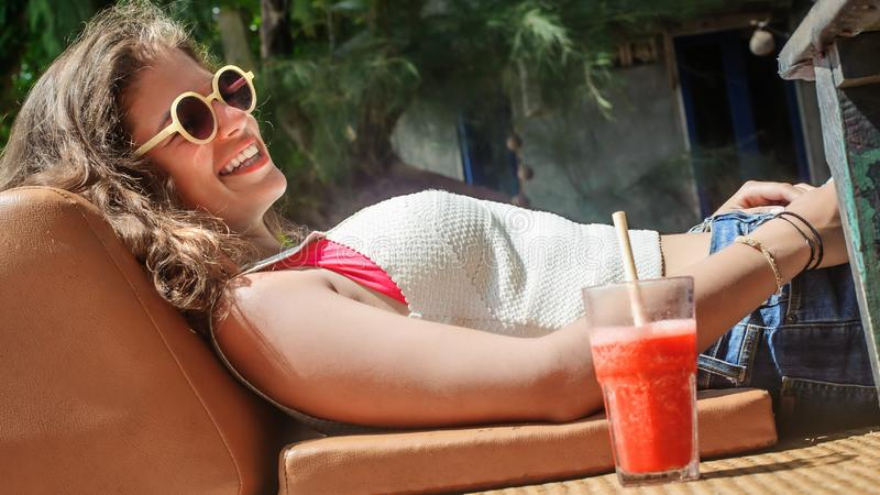 Beautiful young woman drinking fruit cocktail on a tropical beach. Beautiful young woman sitting in bar cafe, drinking fruit cocktail on a tropical beach royalty free stock photography