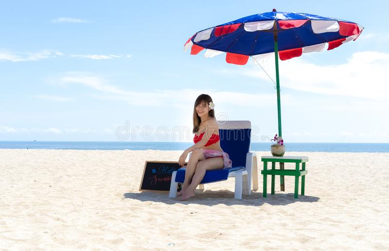 Beautiful young woman sitting on the beach chair under beach umbrella on vacation.Holidays travel concept. royalty free stock photo