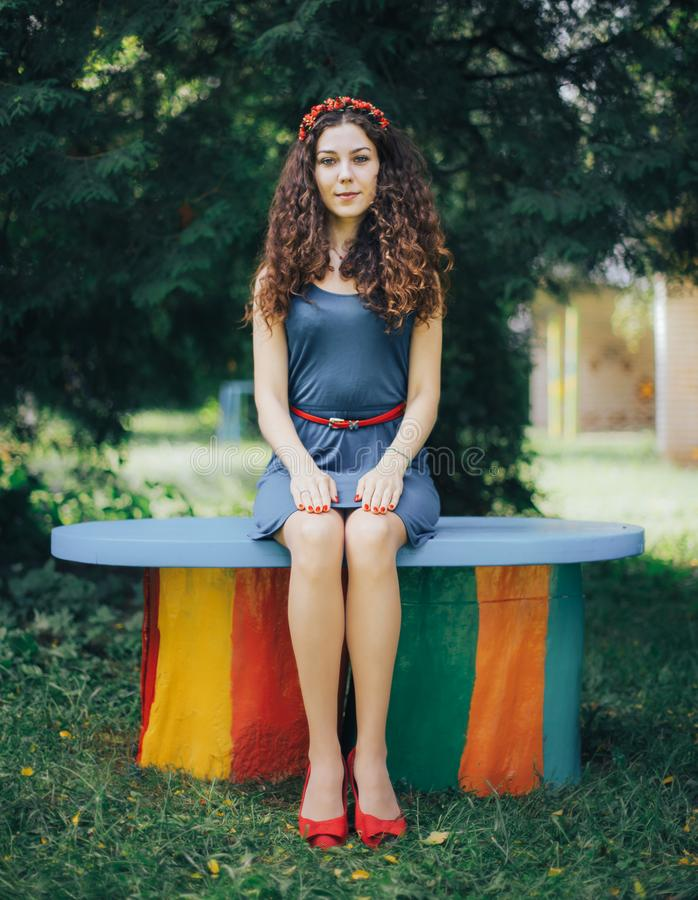 Beautiful young woman sitting on a bench in a park stock photo