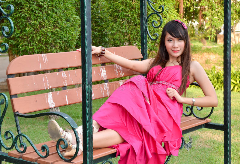 Beautiful young woman sitting on a chair royalty free stock images