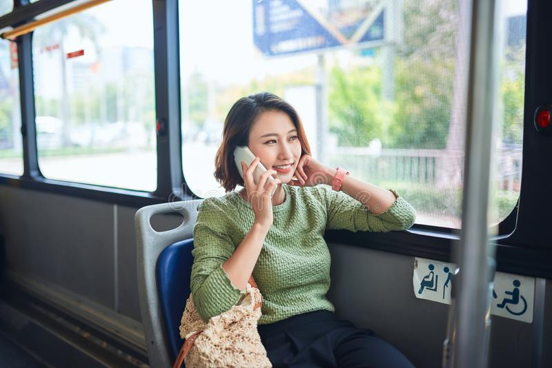 Beautiful young woman sitting in city bus and talking on mobile phone royalty free stock photos