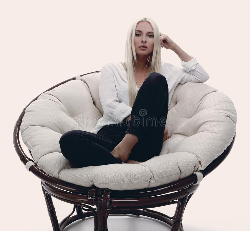 beautiful young woman sitting on the couch in a large comfortabl stock photography