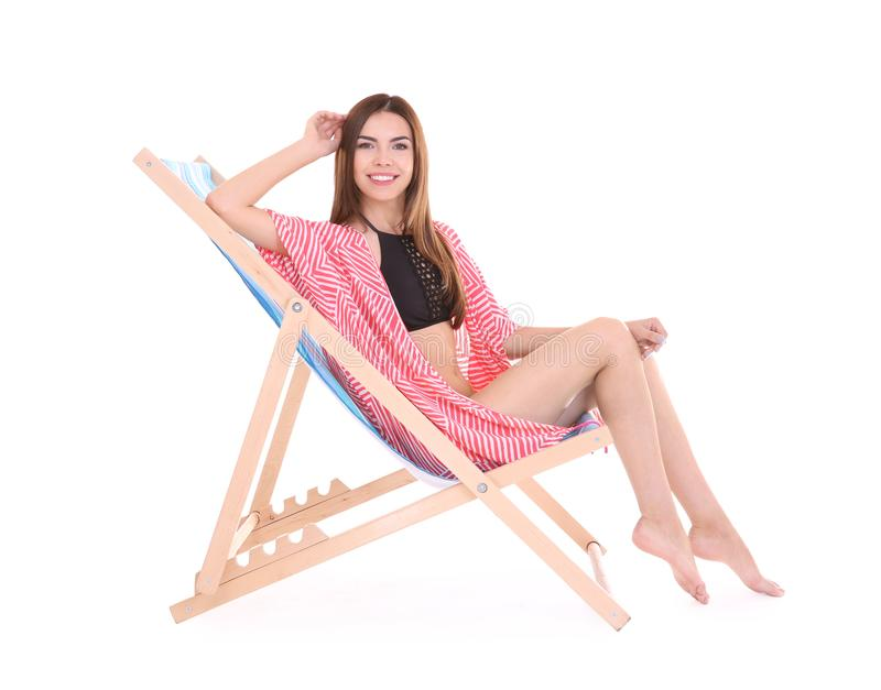 Beautiful young woman sitting on deck chair. Against white background stock photos