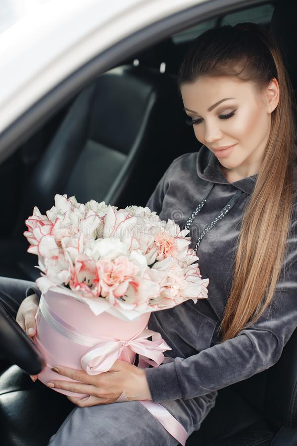 Beautiful young woman, sitting on the driver`s seat in a car with a pink box full of tender, white, with a pink edging of tult-col stock photo
