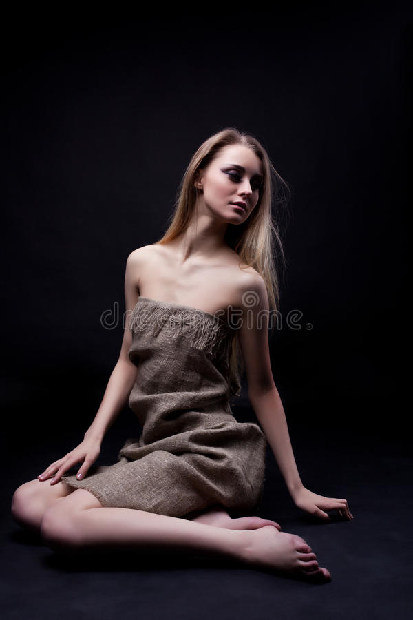 Beautiful young woman sitting on floor royalty free stock photo