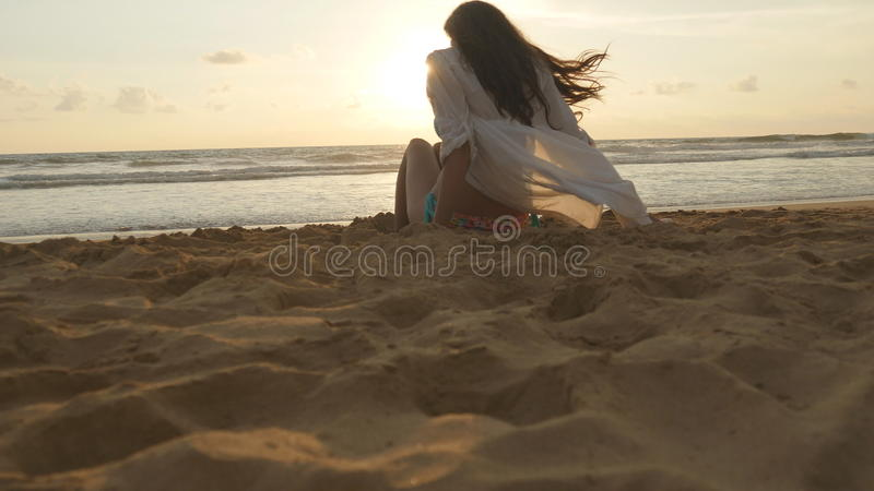 Beautiful young woman sitting on golden sand on sea beach during sunset and calls to himself. Girl relaxing on ocean. Shore during summer vacation travel at stock photo