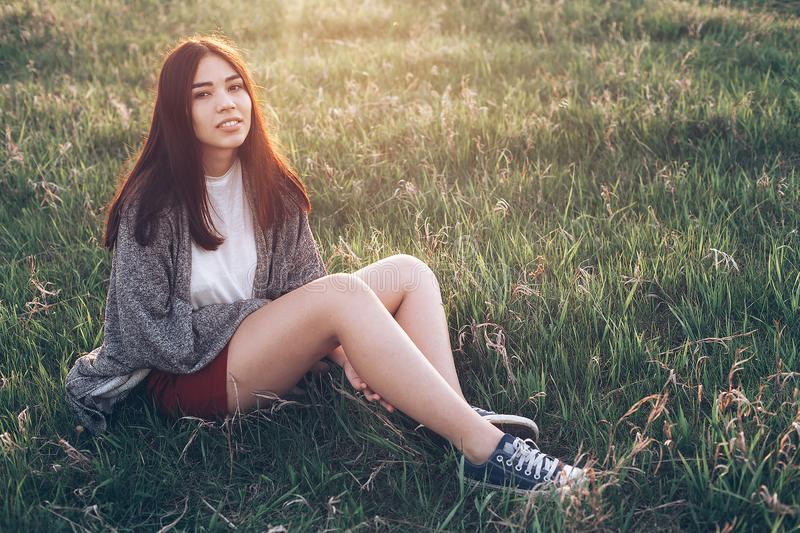 Beautiful young woman sitting on the grass stock photos