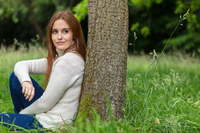 Beautiful Young Woman Sitting Leaning Against Tree. Outdoor portrait of beautiful thoughtful happy girl or young woman with red hair wearing a white jumper stock photos