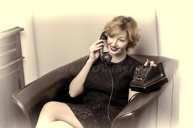 Portrait of young woman talking using a vintage telephone agains royalty free stock image