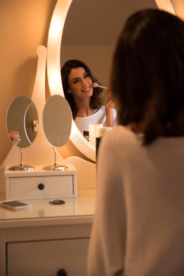 A beautiful young woman at a makeup table royalty free stock photos
