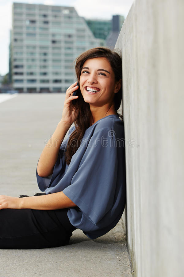 Beautiful young woman sitting outdoors and talking on cell phone. Portrait of beautiful young woman sitting outdoors and talking on cell phone royalty free stock photos