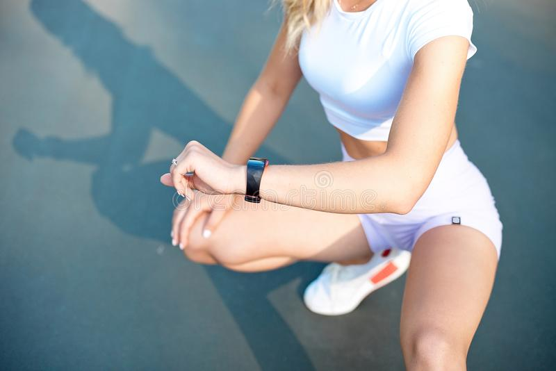 Beautiful young woman sitting outdoors using a smartwatch to monitor her progress. Caucasian female runner resting and royalty free stock images