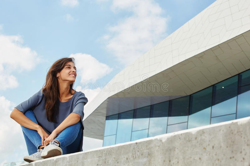 Beautiful young woman sitting outside and looking away. Portrait of beautiful young woman sitting outside and looking away stock photography