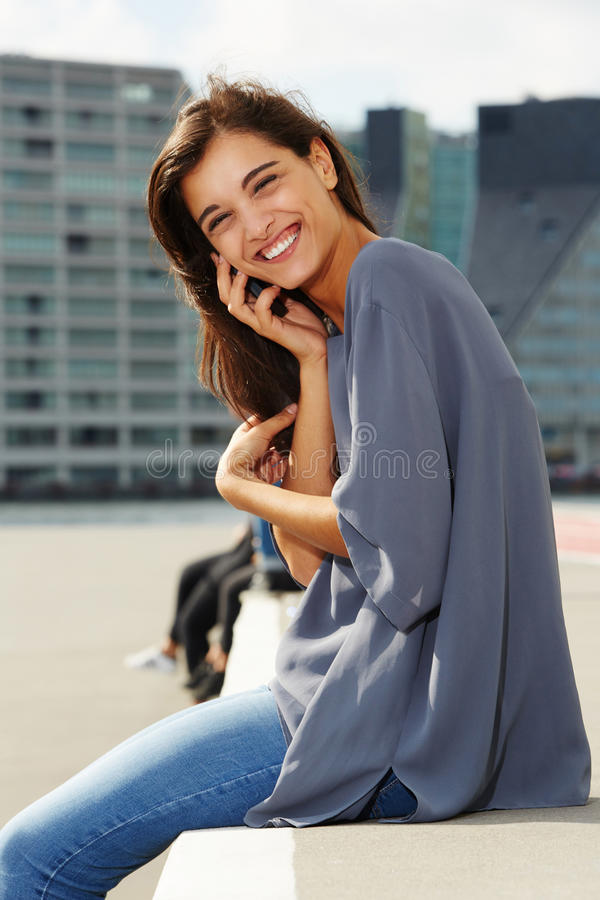 Beautiful young woman sitting outside and talking on mobile phone. Portrait of beautiful young woman sitting outside and talking on mobile phone stock image