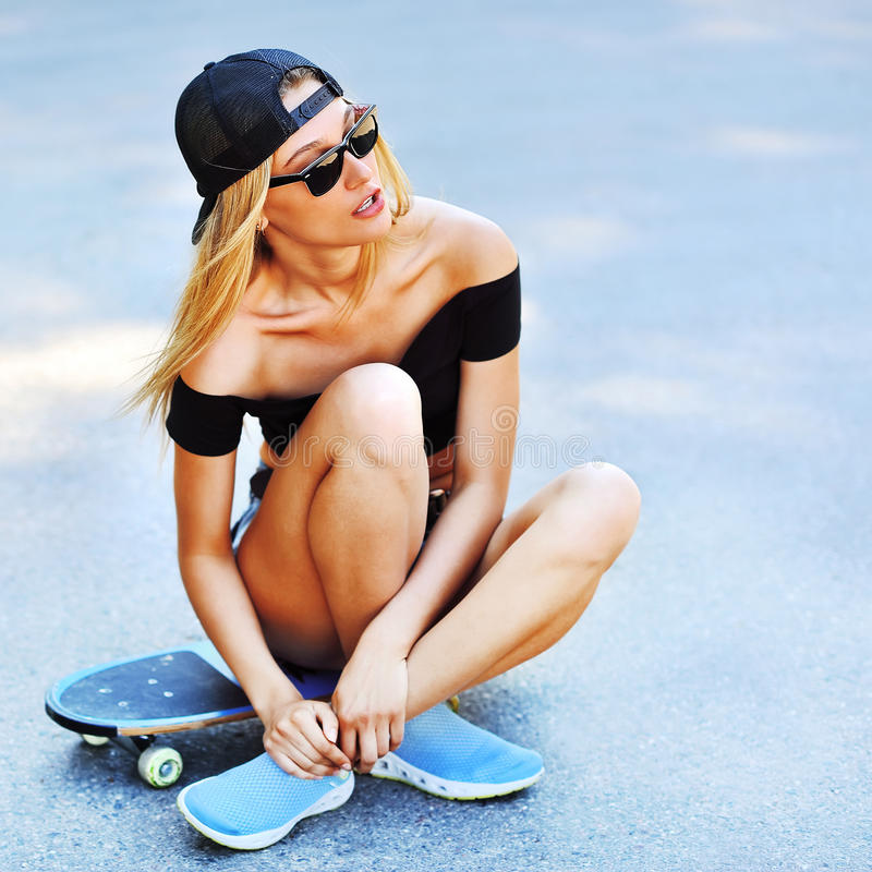 Beautiful young woman sitting over a skateboard. Outdoors royalty free stock image