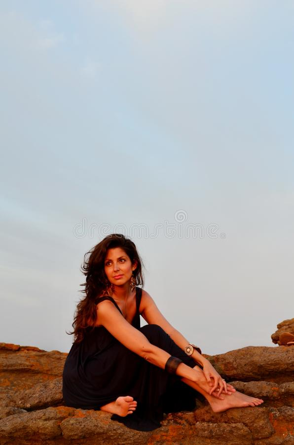 Beautiful Young Woman Sitting on a Rocks above the Sea stock images