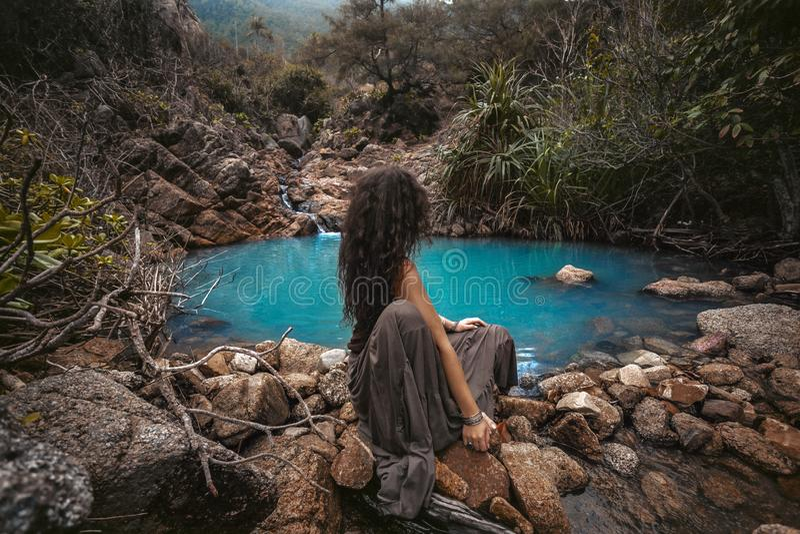 Beautiful young woman sitting at small mountain lake stock photos