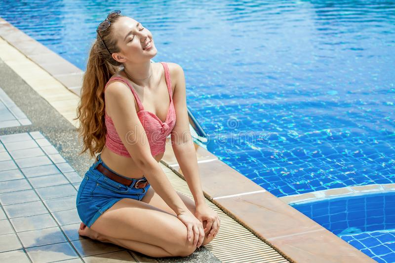 Beautiful young woman sitting sunbathe and relaxation posing by swimming pool outdoors in .sexy female resting in vacation. Attractive, casual, hot, hair royalty free stock image