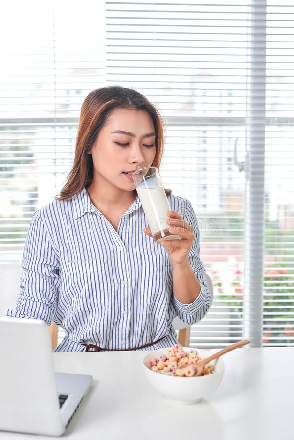 Beautiful young woman sitting at the table in home office, holding glass of milk with cereal, using laptop royalty free stock photos