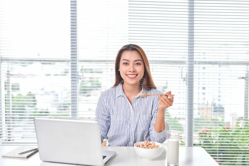 Beautiful young woman sitting at the table in home office, holding glass of milk with cereal, using laptop stock photo