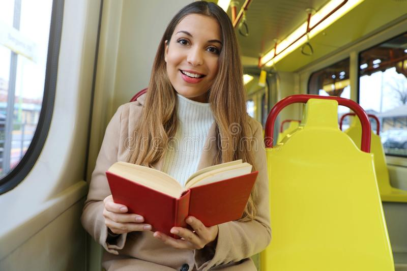 Beautiful young woman sitting in tram caught and surprised at reading her book looks at camera royalty free stock image