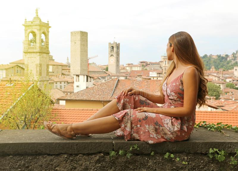 Beautiful young woman sitting on wall looking at italian medieval old town of Bergamo, Italy stock images