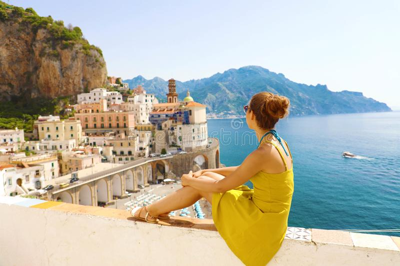 Beautiful young woman sitting on wall looking at stunning panoramic village of Atrani on Amalfi Coast, Italy.  royalty free stock photography