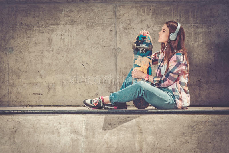Beautiful young woman with skateboard outdoors royalty free stock photos