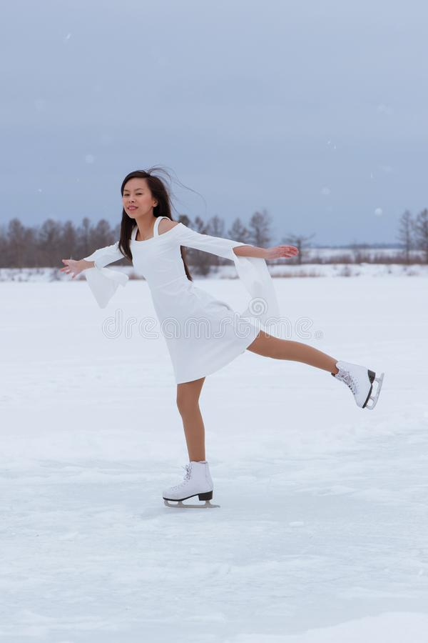 Beautiful young woman on skates. In white dress outdoors at winter snow royalty free stock images