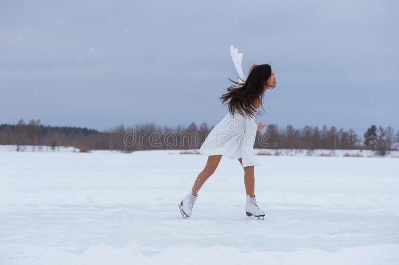 Beautiful young woman on skates. In white dress outdoors at winter snow stock photography