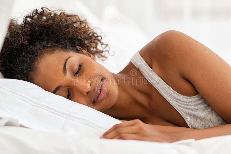 Beautiful african woman sleeping in bed stock image