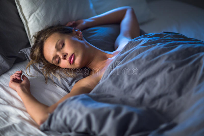 Beautiful young woman sleeping in bed stock photography