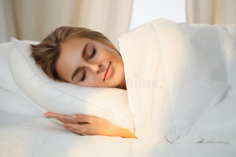 Beautiful young woman sleeping while lying in bed comfortably and blissfully Sunbeam dawn on her face stock image
