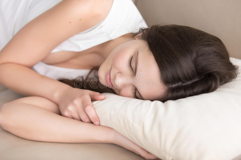 Beautiful young woman sleeping on orthopedic comfortable pillow,. Pretty girl lying asleep on cozy couch cushion, taking nap at home, resting on sofa, enjoying royalty free stock image