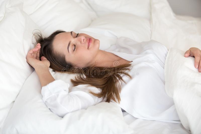 Beautiful young woman sleeping well in cozy comfortable soft bed. Beautiful young woman sleeping well in cozy comfortable bed on soft orthopedic pillow and royalty free stock image