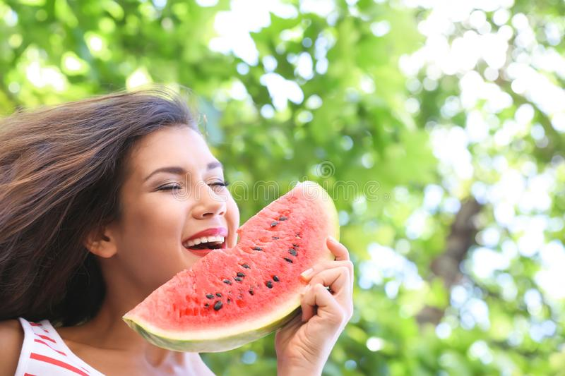 Beautiful young woman with slice of tasty watermelon outdoors royalty free stock images