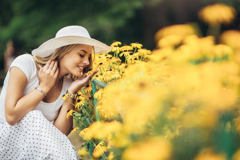 Young woman smelling yellow flower in the park stock image