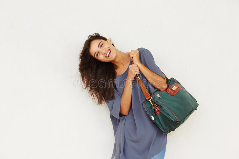 Beautiful young woman smiling with bag against white wall. Portrait of beautiful young woman smiling with bag against white wall stock photography