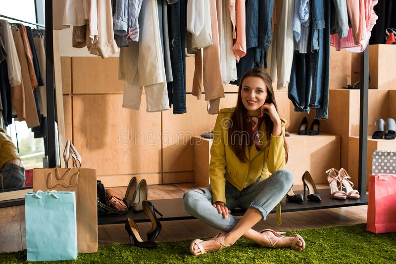 beautiful young woman smiling at camera while choosing shoes and clothes stock photos
