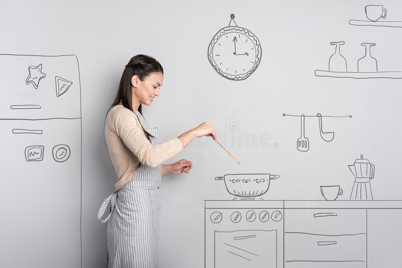 Beautiful young woman smiling while cooking at home royalty free stock photos