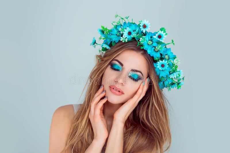 Woman posing with flowers on head blue eyeshadow closed eyes stock images