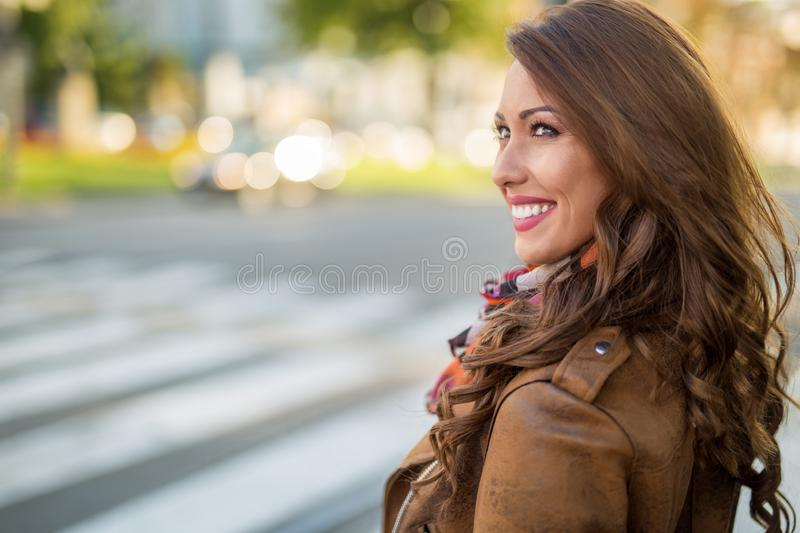 Beautiful young woman smiling while waiting at a cross walk royalty free stock photography